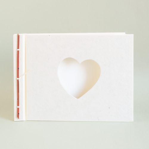 Cremefarbenes Fotoalbum mit herzförmigem Passepartout im Deckel. Orange abgesetzte Japanbindung mit Bambusdekor am Rücken, weisse Fotokartonseiten.