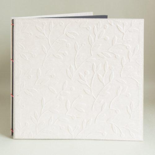 Fotoalbum Naturleinenbezug und Dekor aus geprägtem weissen Büttenpapier, rot abgesetzte Japanbindung, schwarze Fotoseiten mit Trennblättern aus Pergamin.