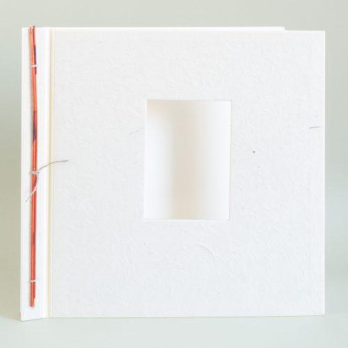 Großes cremefarbenes Fotoalbum mit orange abgesetztem Bambusdekor am Rücken und Fenster im Alben-Deckel